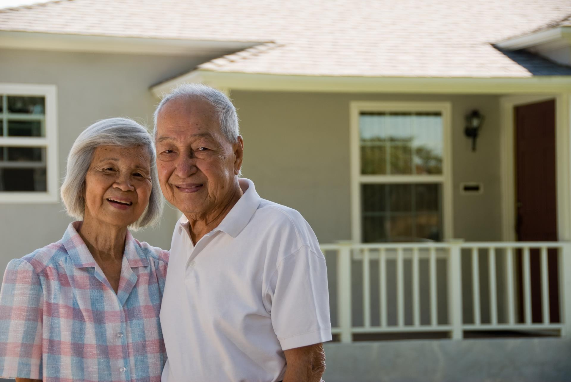 Senior couple in front of house iStock-144320751